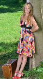 Pretty blonde woman in sundress with suitcase Stock Photo
