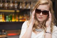 Pretty blonde woman in sunglasses posing Arkivfoto