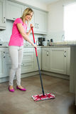 Pretty blonde woman swiping the kitchen floor Royalty Free Stock Images