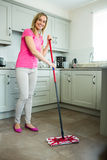 Pretty blonde woman swiping the kitchen floor Stock Image