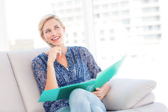 Pretty blonde woman taking notes on the couch Stock Photo