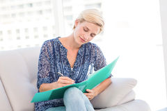 Pretty blonde woman taking notes on the couch Stock Photos