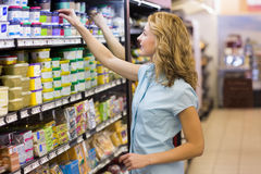 Pretty blonde woman taking a products in shelves. In supermarket Stock Photos