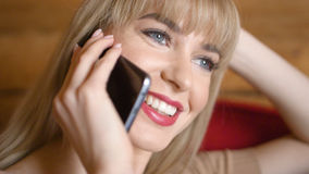 Pretty blonde woman talking on the phone at home. Young woman using phone, indoors Royalty Free Stock Images