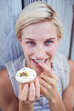 Pretty blonde woman tasting the cupcake Stock Photos