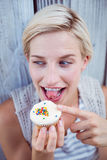 Pretty blonde woman tasting the cupcake Stock Photo