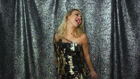 Pretty blonde woman throwing up confetti. Young beautiful woman in glamour dress throwing up confetti and smiling while looking at camera stock footage