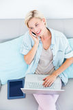 Pretty blonde woman using her laptop while calling on the phone Royalty Free Stock Photos