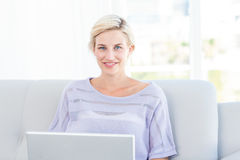 Pretty blonde woman using her laptop on the couch Royalty Free Stock Photography