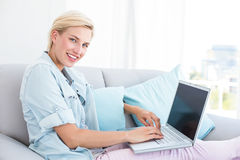Pretty blonde woman using her laptop on the couch Stock Photos