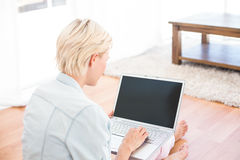 Pretty blonde woman using her laptop on the floor Royalty Free Stock Photography
