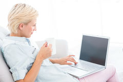 Pretty blonde woman using her laptop and holding mug Royalty Free Stock Image