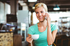 Pretty blonde woman using her smartphone with a cup of coffee Royalty Free Stock Image