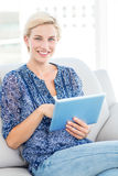Pretty blonde woman using her tablet on the couch Royalty Free Stock Photo