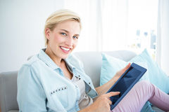 Pretty blonde woman using her tablet on the couch Royalty Free Stock Photos