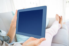 Pretty blonde woman using her tablet on the couch Stock Image