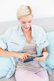 Pretty blonde woman using her tablet on the couch Stock Photo