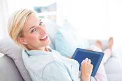 Pretty blonde woman using her tablet on the couch Royalty Free Stock Images