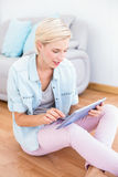 Pretty blonde woman using her tablet on the floor Royalty Free Stock Photo