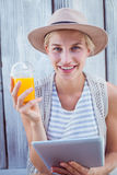 Pretty blonde woman using her tablet and holding orange juice Royalty Free Stock Photography