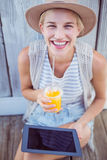 Pretty blonde woman using her tablet and holding orange juice Stock Photography