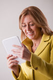 Pretty blonde woman using a tablet Royalty Free Stock Photography