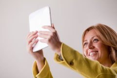 Pretty blonde woman using a tablet Stock Images
