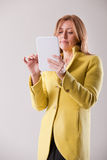 Pretty blonde woman using a tablet Stock Photography