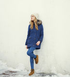 Pretty blonde woman wearing a jacket and hat. In city Stock Photo