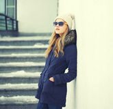 Pretty blonde woman wearing jacket, hat and sunglasses Stock Image