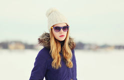 Pretty blonde woman wearing a jacket, hat and sunglasses. Outdoors Royalty Free Stock Image