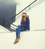 Pretty blonde woman wearing a jacket, hat and sunglasses sitting Stock Images