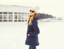 Pretty blonde woman wearing a jacket, hat and sunglasses in winter Stock Images