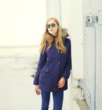 Pretty blonde woman wearing a jacket and sunglasses Stock Photo