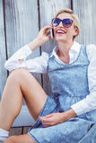 Pretty blonde woman wearing sun glasses and calling on the phone Royalty Free Stock Photography