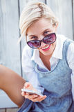 Pretty blonde woman wearing sun glasses and texting with her mobile phone Royalty Free Stock Photography