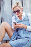 Pretty blonde woman wearing sun glasses and texting with her mobile phone Stock Photography