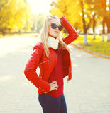 Pretty blonde woman wearing a sunglasses and red jacket with scarf in sunny autumn. Day Royalty Free Stock Photography