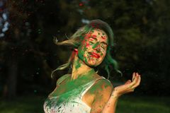 Pretty blonde model wearing white shirt and posing covered with dry paint at the Holi Festival. Pretty blonde woman wearing white shirt and posing covered with royalty free stock images