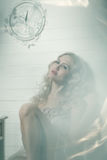 Pretty blonde woman in a white interior. Vintage cold colors with soft effect royalty free stock photography