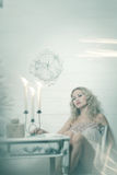 Pretty blonde woman in a white interior. Vintage cold colors with soft effect royalty free stock images