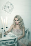 Pretty blonde woman in a white interior. Vintage cold colors with soft effect stock photos