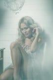 Pretty blonde woman in a white interior Stock Photo