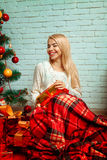 Pretty blonde wrapped plaid with a bunch of Christmas presents s Royalty Free Stock Photography