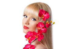 Pretty blonde young girl with red orchid flowers Stock Images
