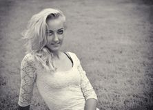 Pretty blonde young woman outdoor laying down on grass Stock Photo