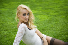 Pretty blonde young woman outdoor laying down on grass. Pretty blonde young woman outdoor in white dress laying down on lush green grass Royalty Free Stock Image