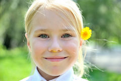 Pretty blone girl outdoors with flower behind ear. Close-up portraite of pretty blone girl outdoors with flower behind ear Royalty Free Stock Photo