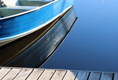 Pretty blue boat at the dock's edge Stock Images