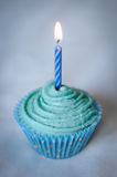 Pretty Blue Cupcake with Blue Candle on top. Pretty Blue Iced Cupcake for a birthday or celebration with a Blue Candle burning on top Stock Image